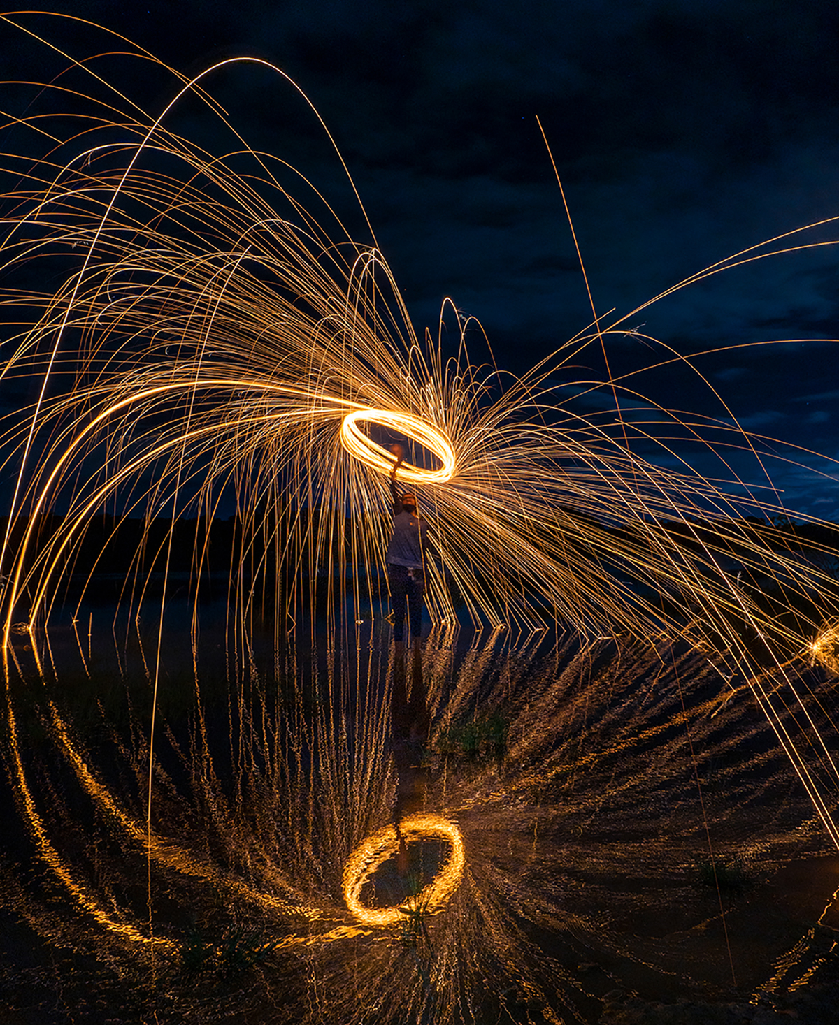A photo taken at night at a lake in Bengaluru, India. A friend is wielding a rope of steel wool on fire. He is standing on the banks of the lake and the brilliant luminescence of the steel wool is reflected over the water.