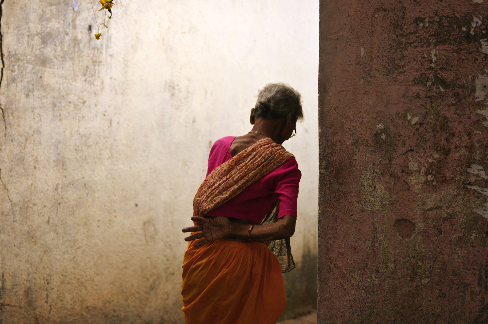 Photo by Kristian Bertel - An alley or alleyway is a narrow lane, path or passageway, often reserved for pedestrians, which usually runs between, behind or within buildings in the older parts of towns and cities. Here the photographer captured his participating image for the contest of a woman passing through an alley in Mumbai, India.