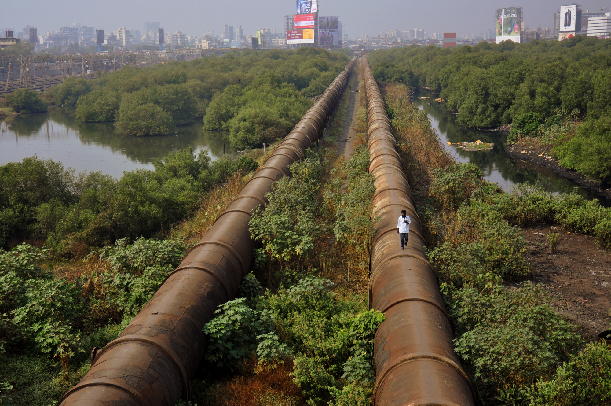 Photo by Kristian Bertel - A giant water pipeline runs along one of Dharavi's rubbish-filled canals in Mumbai, India. As Mumbai's population grows, the demand on the city's existing infrastructure increases exponentially and their water supply is finding it difficult to keep up.