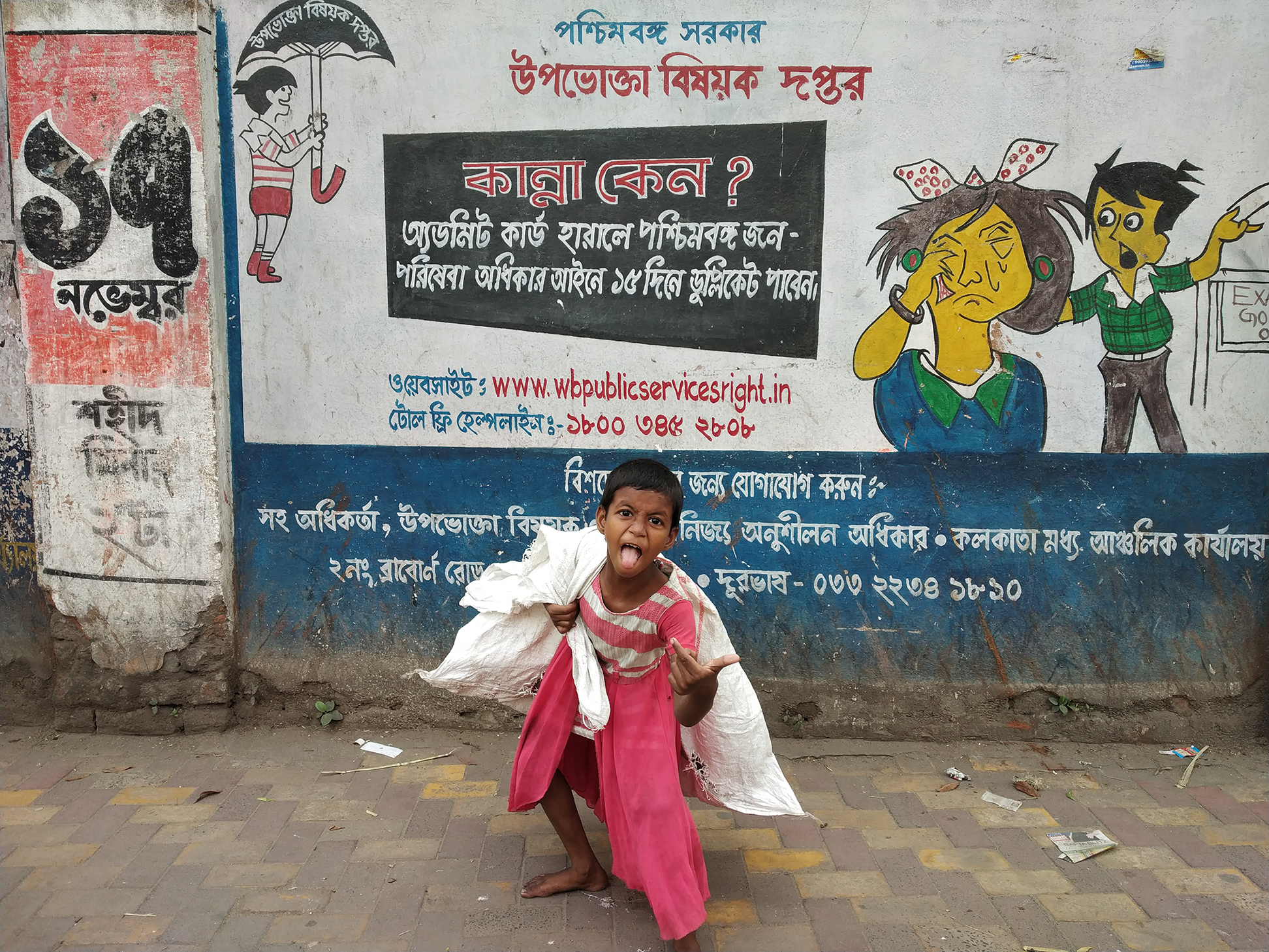 It was a cloudy afternoon in Kolkata. I was hopping into central Kolkata with my friend for street photography. I saw some street children were gossiping among themselves. I have an eye contact with this little girl and we exchange a smile to each other. Then I go forward and saw a wall painting advertisement by West Bengal Govt. Somehow this advertisement and the surroundings with the street people and their children is not appropriate. I take two snap before this  picture. People were passing in front of this wall. Then suddenly that girl who collect the plastic, picked her sack came in front of my camera and give me a funny dont care attitude to me and the society as well. I don't miss this moment to capture it.