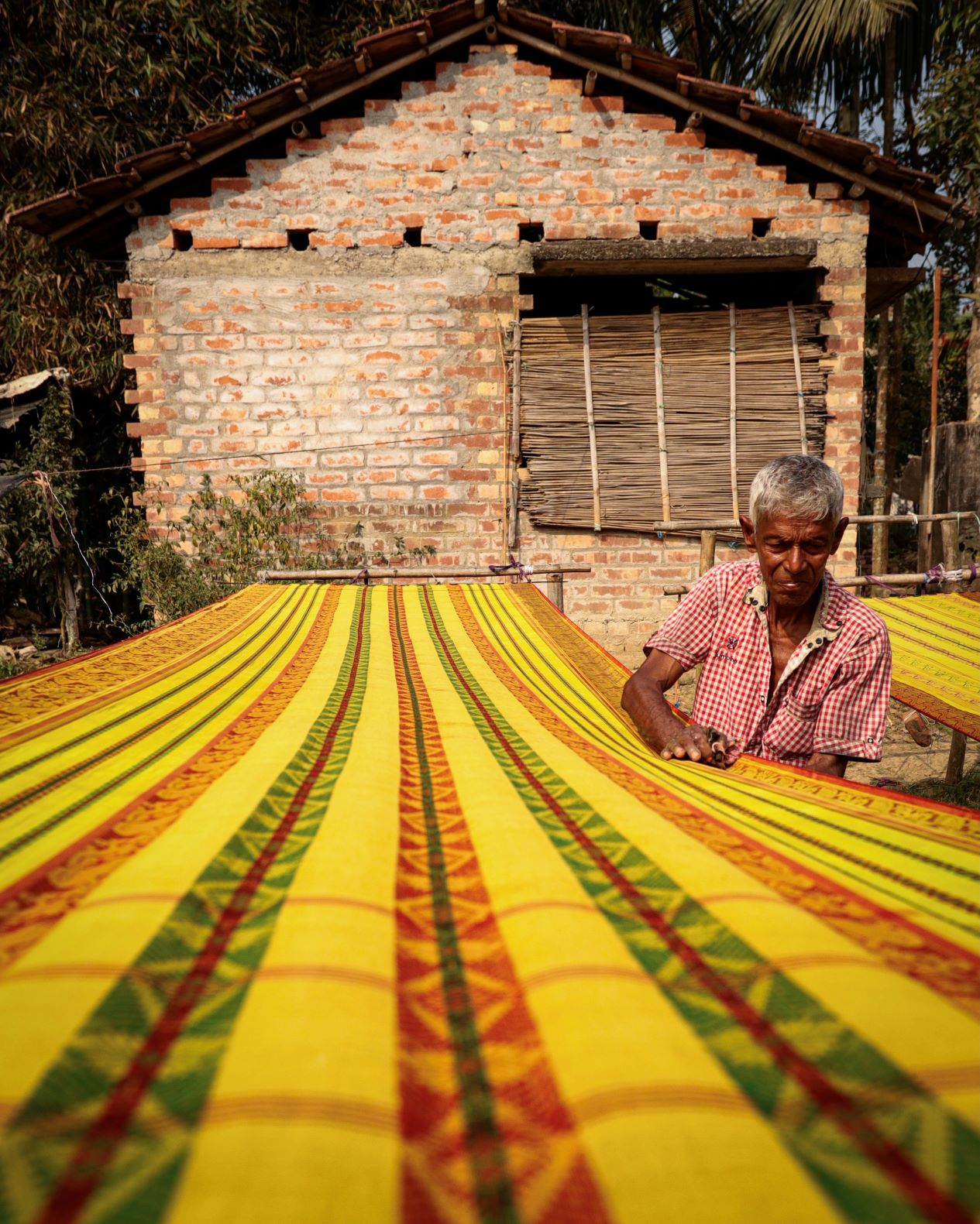 A man cleaning saree and making it ready for selling in the market. Shantipur is known for dyeing process and making of sarees