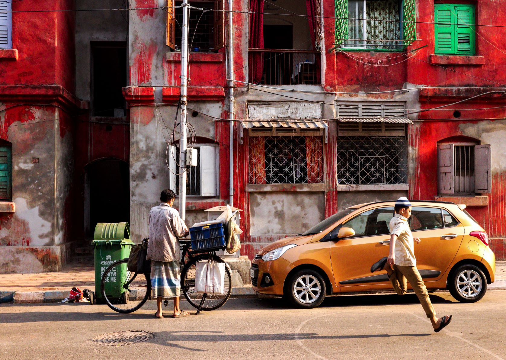A man selling bread and a boy playing in the bow barrack area of Kolkata