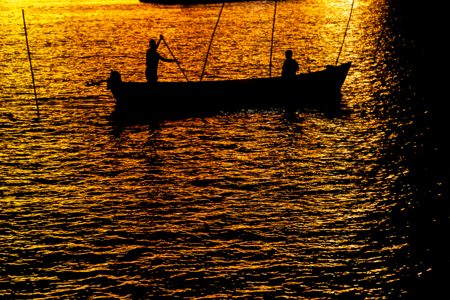 Two fishermen fishing their dinner, in the lights of the giant casino cruises in the background.  I liked the colors, the silhouette of the fishermen. I