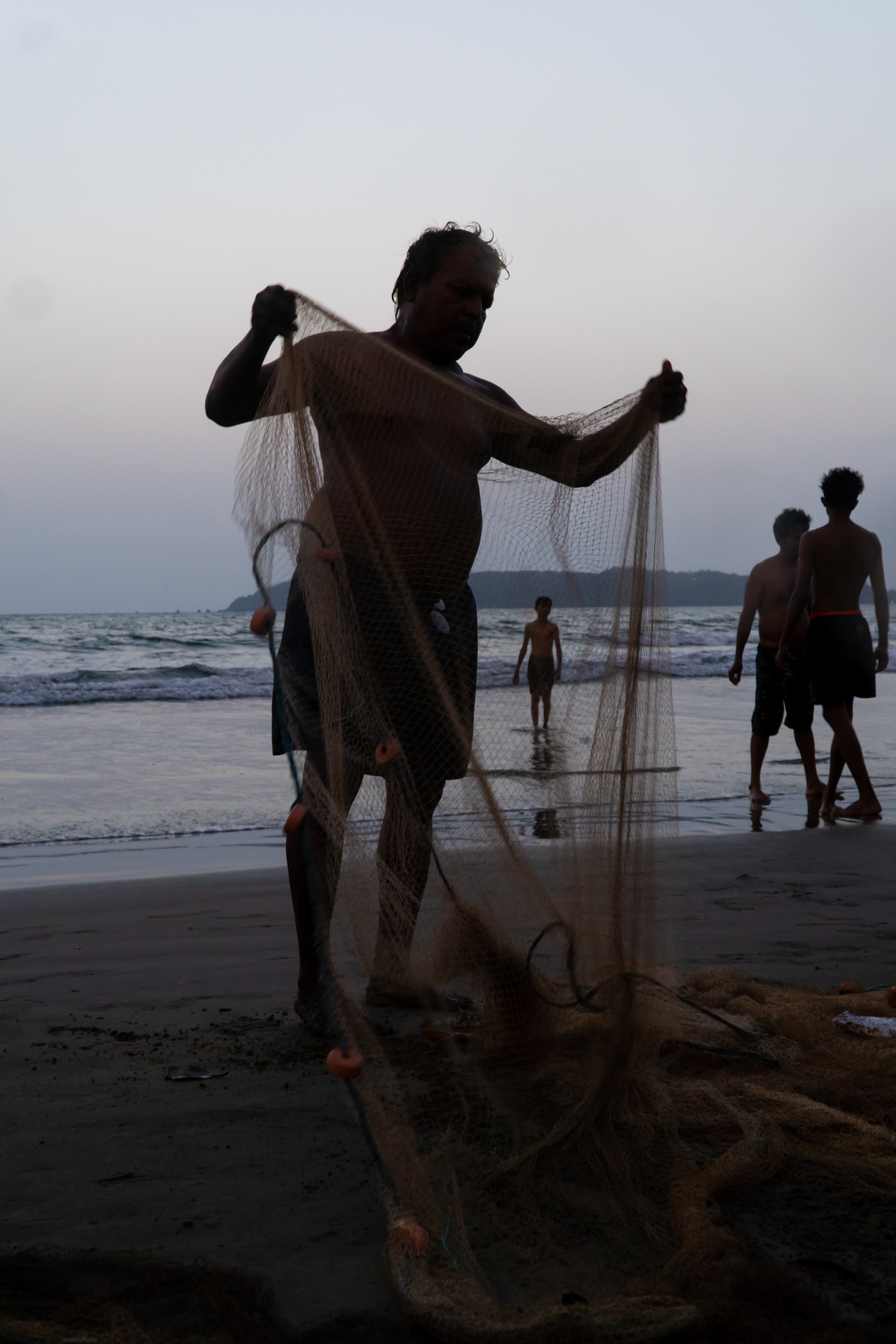 After fishing, this fisherman was  folding his net together, when i noticed the person in background. It seemed that the fisherman had caught the human which was interesting for me.