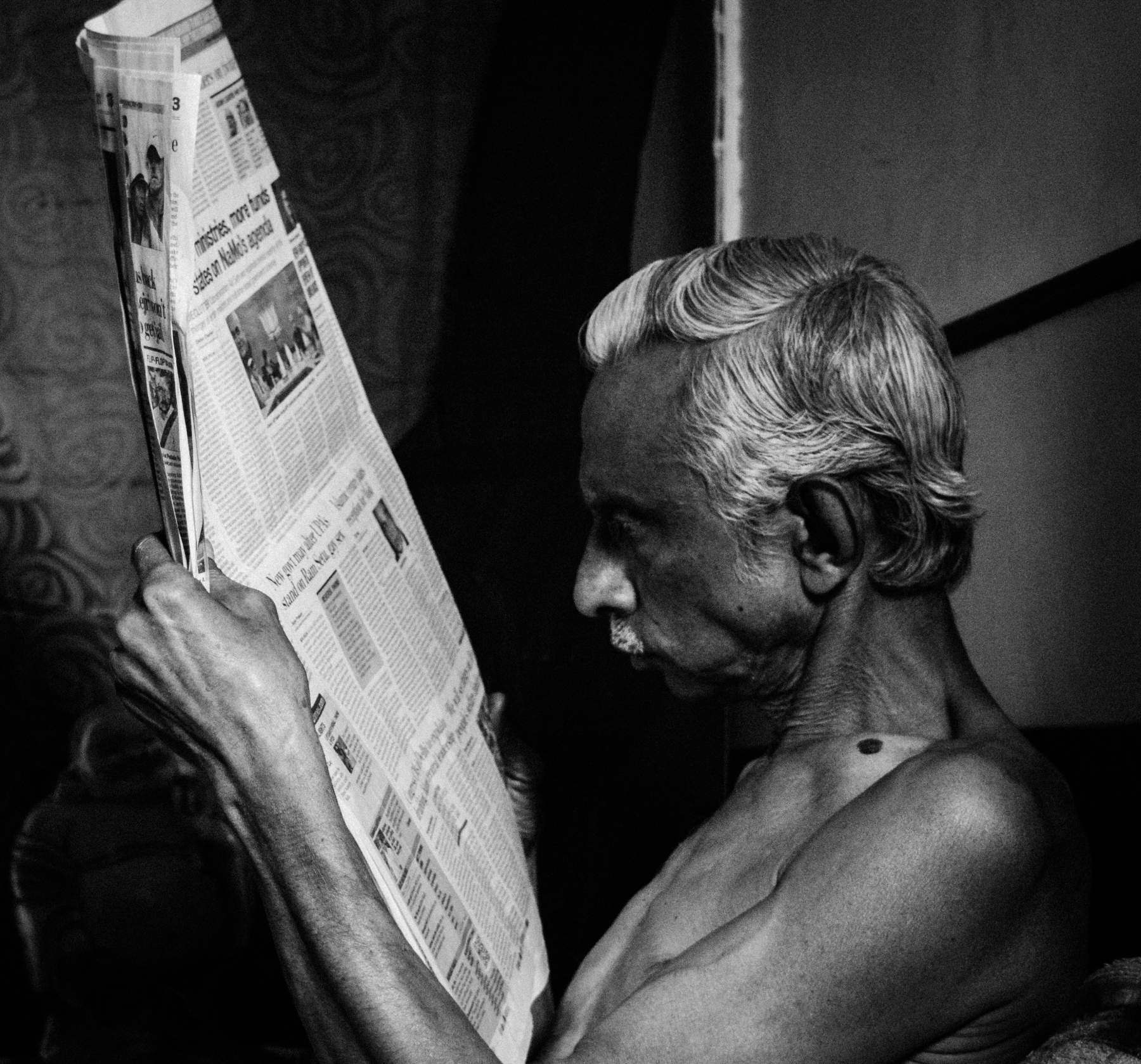 My father is an avid newspaper reader. I saw him engrossed in it so much, that I couldn't resist myself. I asked him to stay still and keep doing what he is doing and I switched the light off and opened the curtain of the window slightly.