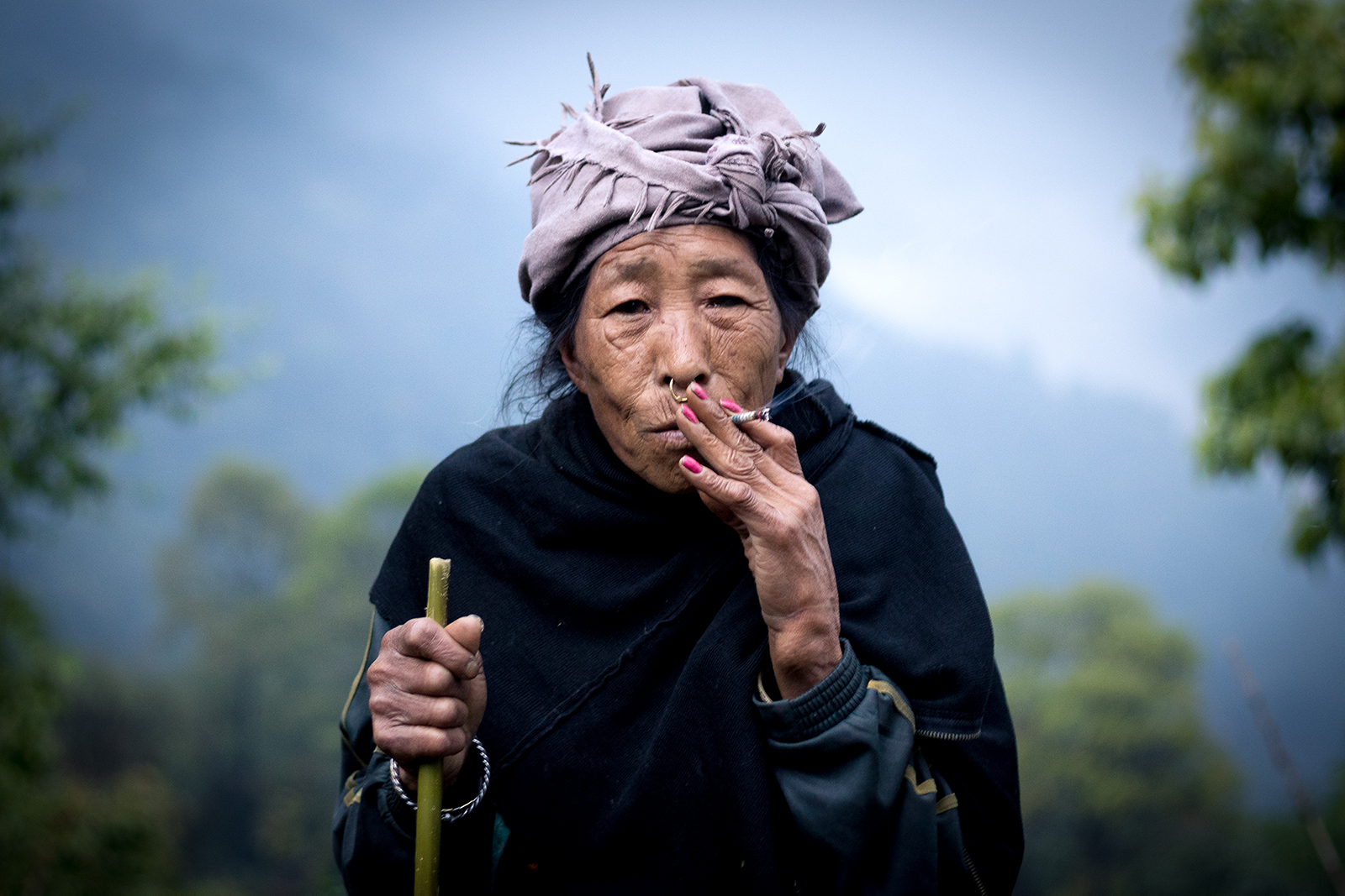 An elderly woman of Limbu community of West Sikkim, smoking on local weed.