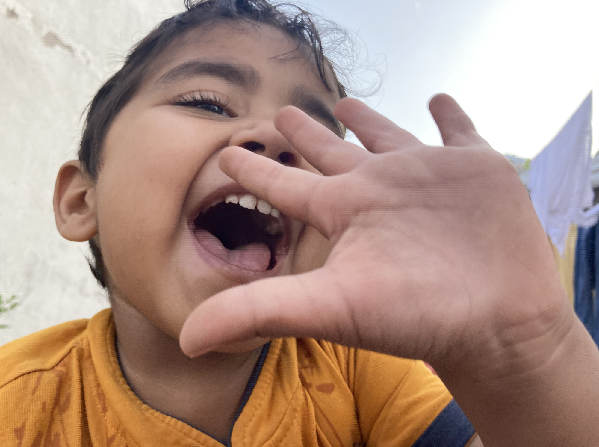 My nephew playing and making noise around. I took this photo when came near me and making different sounds. The wide-angle lens of the phone camera made this image more three dimensional and made it dynamic.