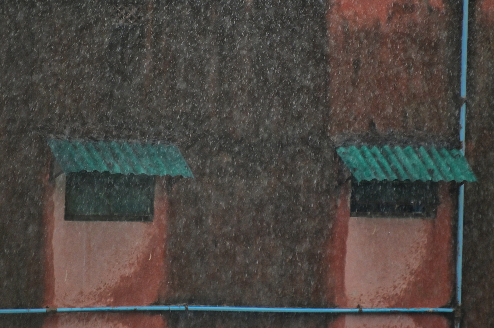 Shot was taken from my window in a rainy day. The two windows, green sheds and the water pipes makes the picture like pastel drawing painting.