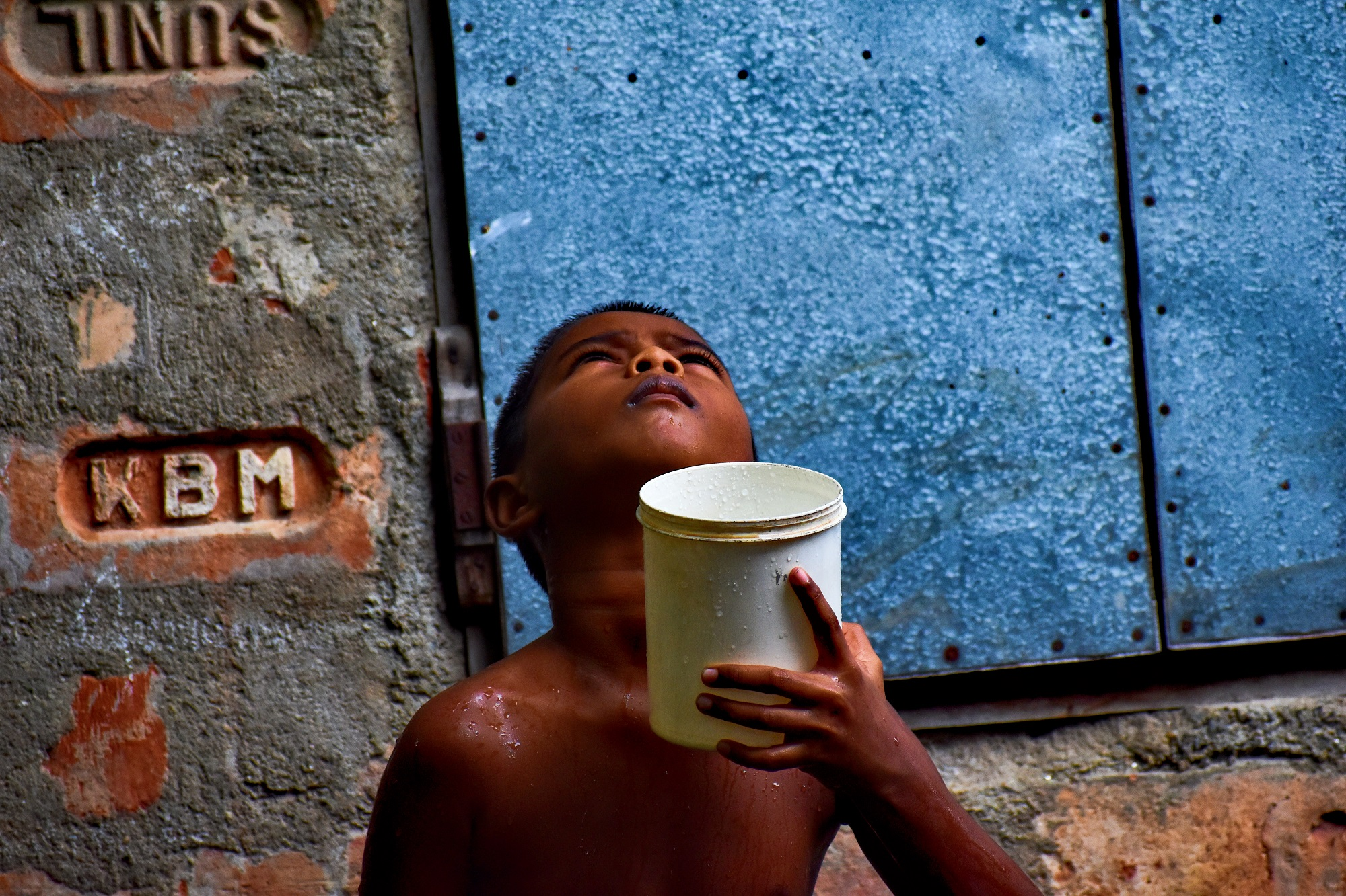 This kid was bathing in the rain when it suddenly stopped. Then he brought out his mug to catch the next drop that would fall. In the picture, he can be seen looking eagerly at the clouds for the next drop.