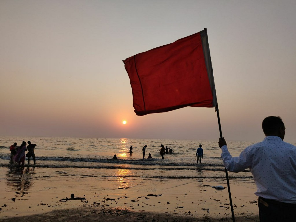 Person holding a flag at the beach.