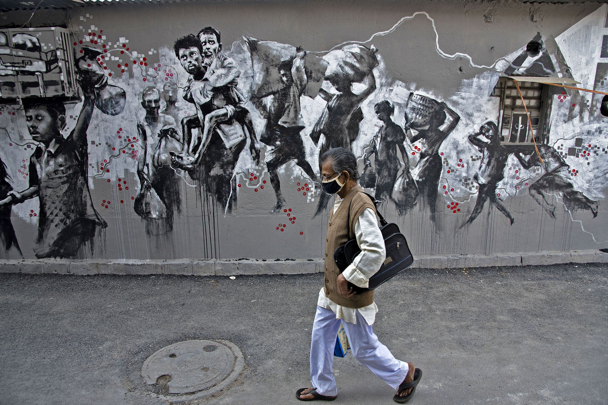 An elderly citizen walks in front of a graffiti depicting the troublesome days of the pandemic with which we are still fighting.