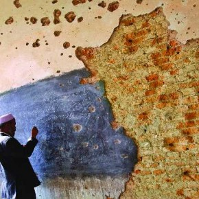 An instructor at Habibia High School in west Kabul writes on a bullet-riddled blackboard. The school was once a major battleground during civil war fighting in the 1990s. Photograph/Benjamin Krain
