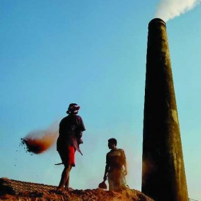 The chimney, the men, the smoke and the dirt falling off the shovel, convey a working environment close to a factory. Photograph/Debasis Majumder