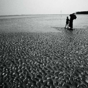 The repeating, rhythmic pattern of the sand directs one's eyes towards the two figures standing on the beach. Photograph/Suman Chatterjee