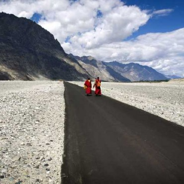 Two monks have been captured midway through their walk down a long, desolate road, effectively conveying the remoteness of the terrain and the length of the monks' journey. Photograph/Ajay Jain