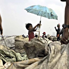 Morsi promised this boy's father that he would keep an eye on him at the Stung Menchey rubbish dump, outside Phnom Penh, Cambodia. He shot this image of the child discovering an umbrella in the dump. Photography by/Mohammed Massoud Morsi