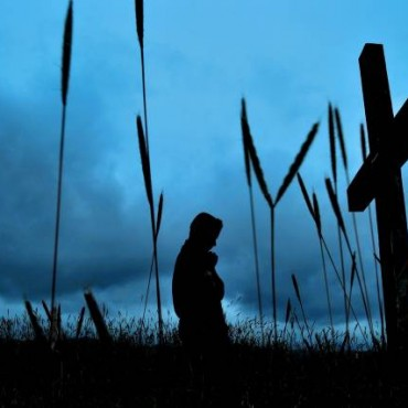 "Title: The Eternal Prayer ""While shooting this image, I chose this low angle to highlight the cross and the profile of the man. I used the grass in the foreground to add drama to the overall composition."" Camera: Nikon D60 ISO: 400 Aperture: f/22 Shutterspeed: 1/80sec Photograph/Vishnu Kudamaloor"