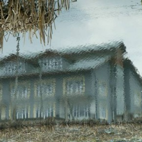"""Title: Topsy Turvy """"One winter, I came across this portion of wetland on the outskirts of Srinagar city. My eyes went to the portion where the water had frozen partially and the wind was blowing. A reflection of a residential house on the shore made this more abstract."""" Camera: Canon EOS 1Ds ISO: 400 Aperture: f/8 Shutterspeed: 1/128sec Photograph/Yawar Nazir, Jammu and Kashmir"""