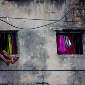 """Title: Made for Each Other """"This image was shot in Kolkata. The house was a small room, evidently with more than one person living inside and unbearably hot in summer. Yet life finds a way and the man managed to relax in the heat."""" Camera: Canon EOS 450D Lens: Canon EF-S 55–250mm IS ISO: 100 Aperture: f/5.6 Shutterspeed: 1/45sec Photograph/Rajarshi Chowdhury, Bengaluru"""