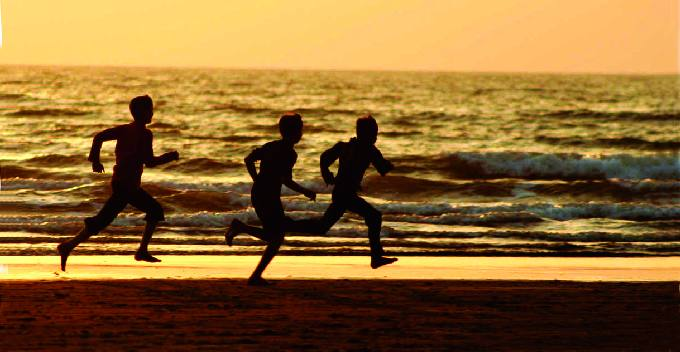 The Three Figures Of Children Running On Beach Add To An Otherwise Plain Shot