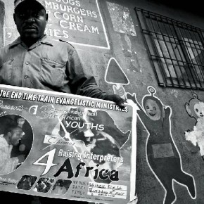 Joshua holds up a poster for his church in front of his barracks where he once murdered and tortured people. Photograph/ Ryan Lobo