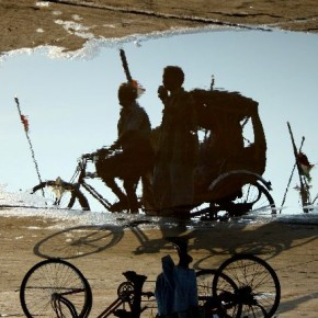 """Title: Triplet. """"The cycle-rickshaw's wheels, its early morning shadow and its reflection in the puddle fit rather well in this beautiful composition. This is why I named it Triplet."""" Camera: Canon EOS 1000D Lens: Canon 55mm Aperture: f/5.6 Shutterspeed: 1/500sec ISO: 100 Photograph/ Ar M Senthil, Chennai"""