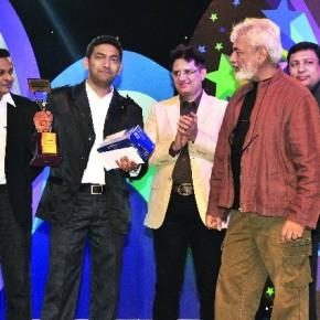 The winner of Fun Frames 2011, Rajiv Kumar Solanki, accepts his award from photographer Dinesh Khanna.