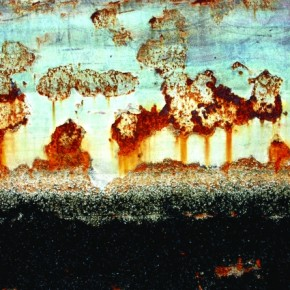The side of a boat is covered with striking rusty oranges, whites and blacks made by water damage. Photograph/Pål Gladsø