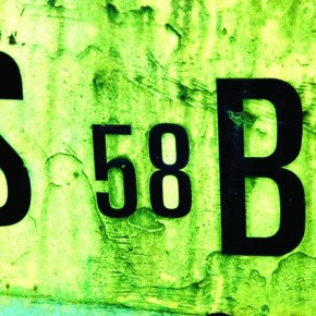 The strong black lines of the letters and numbers contrast strongly with the green hues of the pitted, rusty surface of a dumpster in a junkyard. Photograph/Pål Gladsø