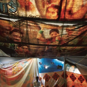 Shot in Pusegaon village, Maharashtra, this picture shows the fashionably modified walls and roofs of the tent have been constructed from discarded posters.