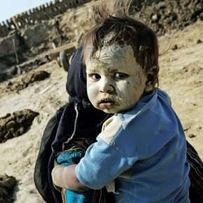 A mother covers her 18-month-old child with wet mud to protect her from the excessive heat coming from the brick kiln. Photograph/Harish Tyagi