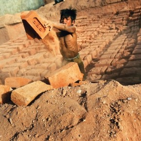 A 9-year-old boy unloads bricks from a kiln. Migrant workers involve their entire family to reduce production time. Plus, the more bricks they make, the more money they get. Photograph/Harish Tyagi