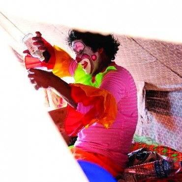 Clown Biju enjoys his local liquor in his tent during a Pune show. He drinks almost everyday. I shot this picture through a torn tent one afternoon. Photograph/Arul Horizon