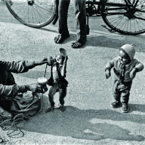 A street performer nudges his monkey to dance along with a child, who has no trouble dancing at all! This was published in the Foto Almanach International (1969, Germany ) Photograph/ S Paul