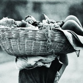 A labourer carries her child in a basket while she goes to work. Photograph/ S Paul