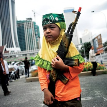 Kuala Lumpur: A child wearing head band with the word Allah written on it holds a toy rifle, during a protest against Israel's attack on Gaza, in front of a US embassy. Photograph/Abdul Rahman Roslan