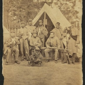 Life in Camp Cameron. Uniformed soldiers with guns in front of a tent; an African American child sits ahead of the group, 1861. Photograph/Mathew B Brady