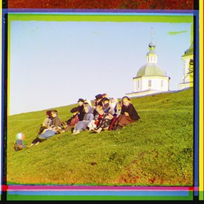 Russian children sit on the side of a hill near a church and bell tower near White Lake, in Russia, 1909. Photograph/S M Prokudin-Gorsky