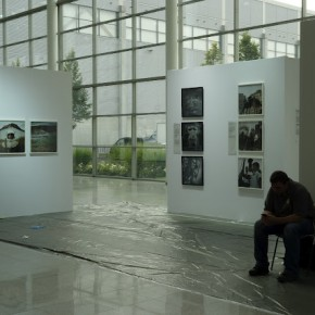 A visitor rests near a photo exhibit.