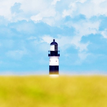 The lighthouse is located in a peninsula and close to buildings on the land. I lowered the camera close to the grass and zoomed all the way to 300mm. Photograph/Alves Filho