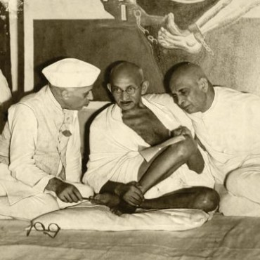 Photograph/Kulwant Singh, Aditya Arya Archive. Mahatma Gandhi, Jawaharlal Nehru and Sardar Vallabhbhai Patel sit in front of the Gulami motif. 1940, shot with a Grafflex system and flash.