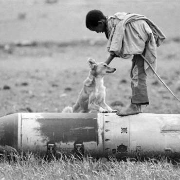 Federal Democratic Republic of Ethiopia, 1991: A young shepherd plays with his dog around an unexploded bomb dropped by forces in Tigray, north Ethiopia.