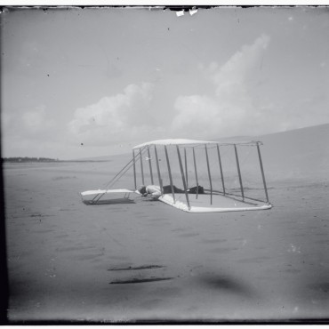 Kitty Hawk, 1903: Wilbur lying flat in a damaged machine after an unsuccessful trial.
