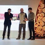 Vasant Bhandari, Head of Events, UB Group and Pulin Soni, Vice President of Photoquip India Ltd present Abhishek Scariya with his award.